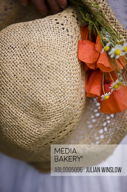 Extreme close up of a straw hat with red poppies and camomile flowers