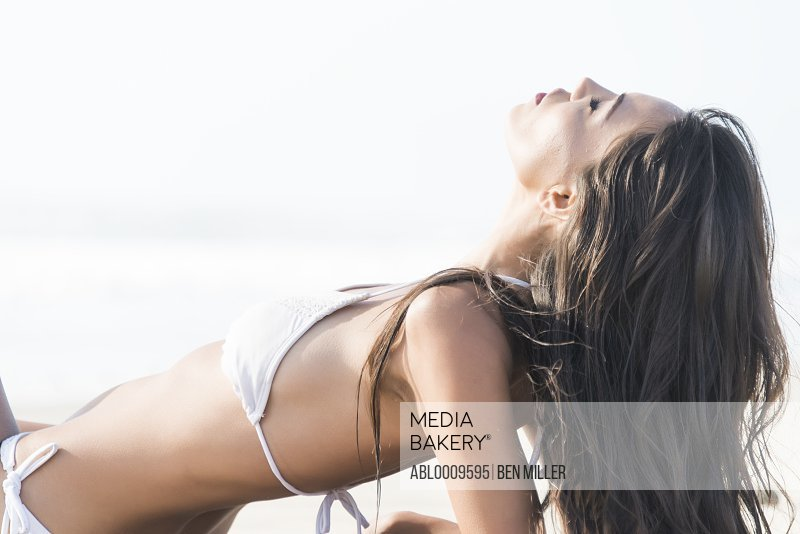 Woman Sunbathing on Beach, Side View