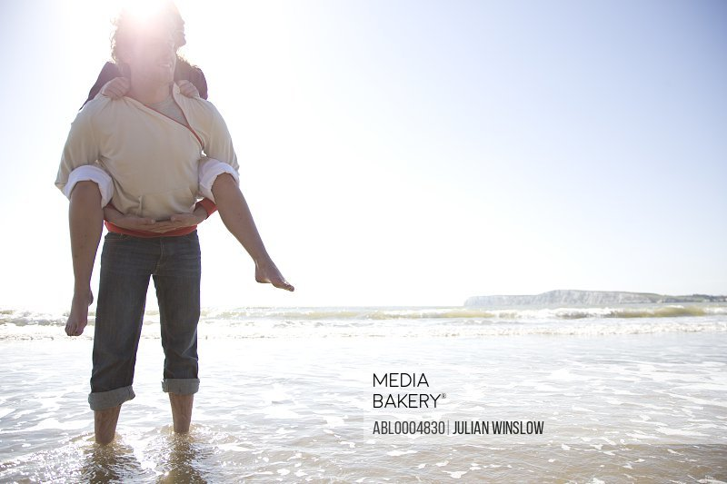 Man carrying woman on his back standing in the sea