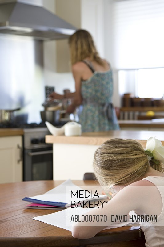 Back View of Young Girl Doing Homework in Kitchen