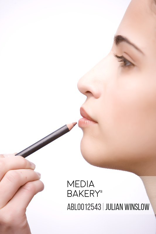 Profile of a young woman applying make on her lips with a lip pencil