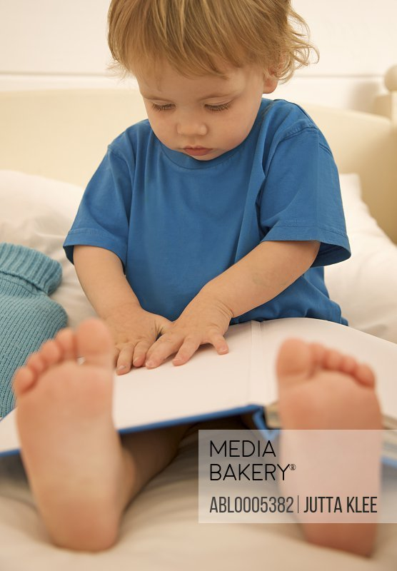 Young boy sitting in bed with an open book over is legs and feet