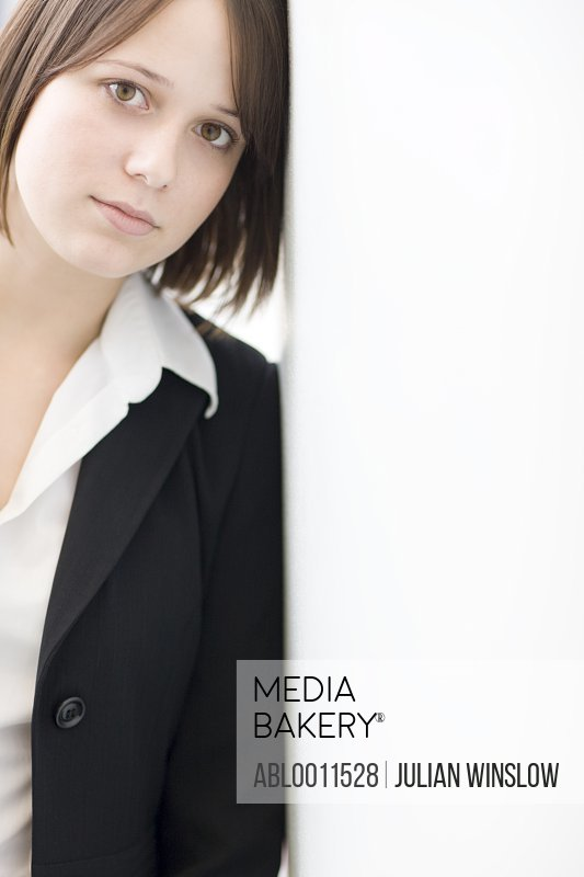 Portrait of young businesswoman leaning against wall