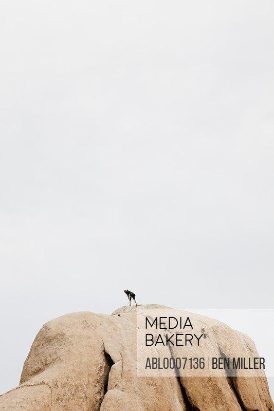 Rock Climber On Top Of Boulder