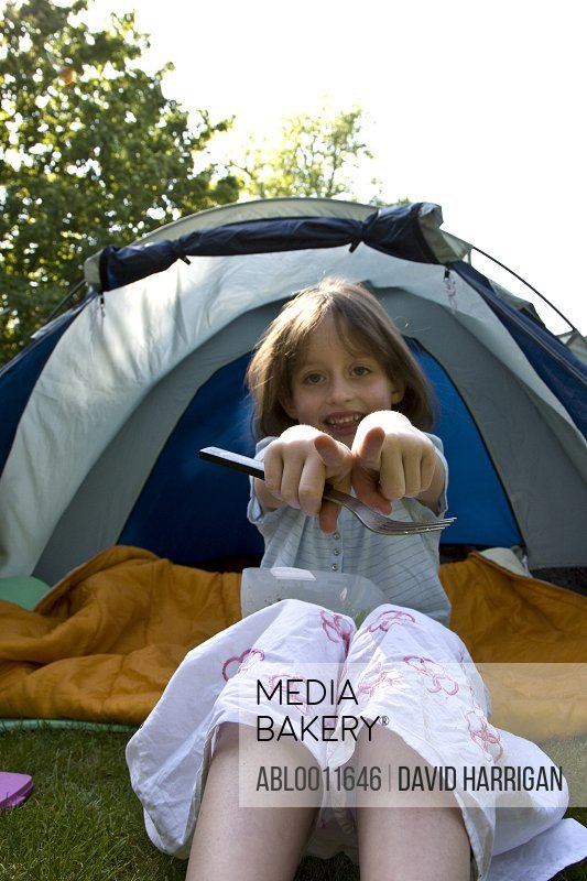 Young girl sitting by tent entrance pointing and holding fork