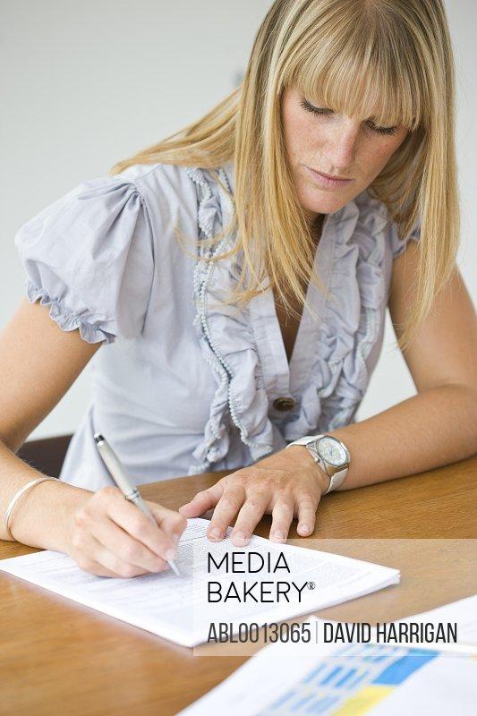 Businesswoman Signing Paperwork