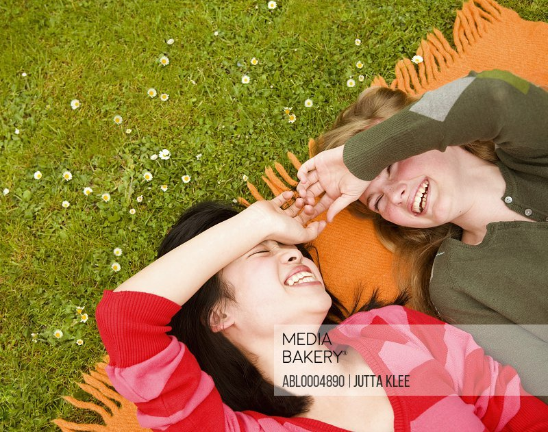 Two teenaged girls laughing and lying on a blanket on a lawn holding hands