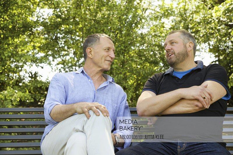 Two Men Sitting on Park Bench Talking