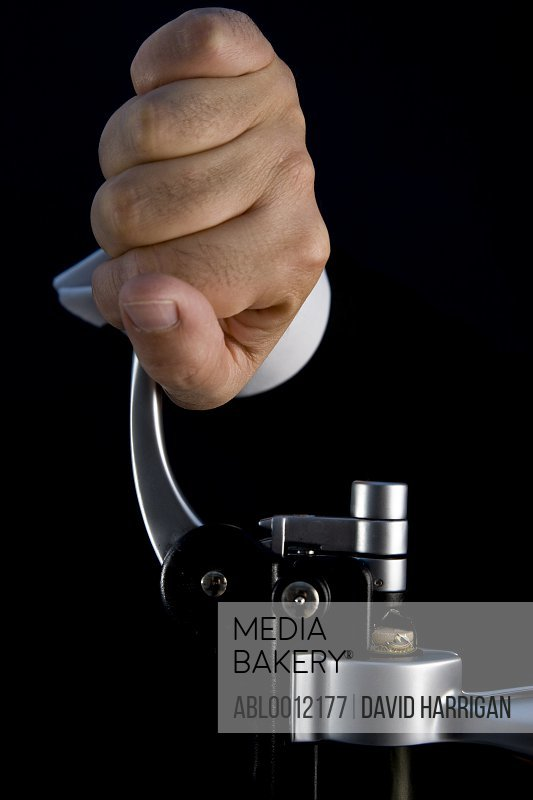 Close up of a waiter hands opening a bottle of wine with a screw pull lever corkscrew