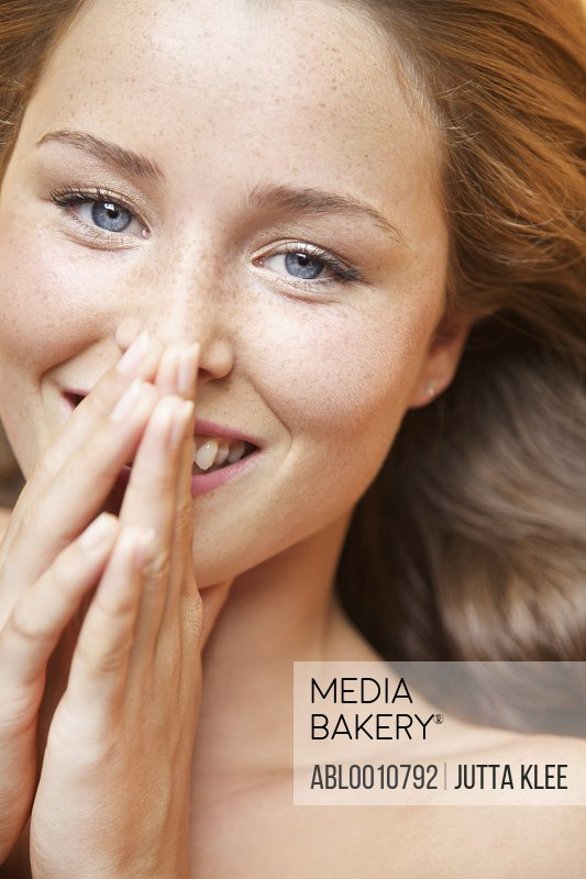 Close up of Young Woman with Hands over Mouth Smiling