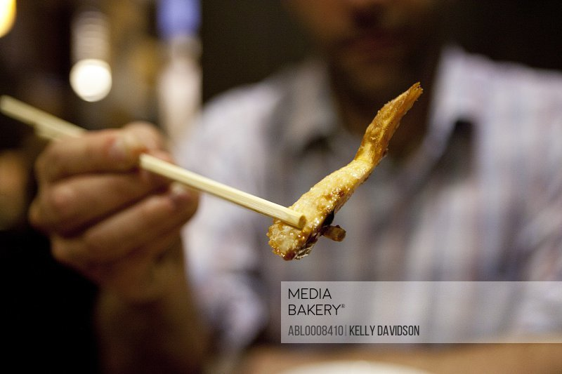 Man Holding a Piece Vegetable Tempura with Chopsticks
