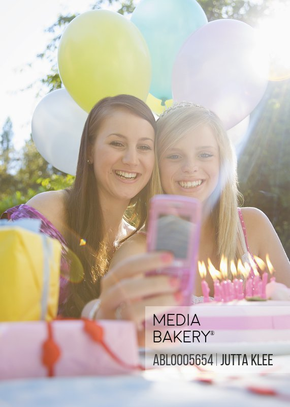 Teenage girls at birthday party taking a self portrait  with mobile phone