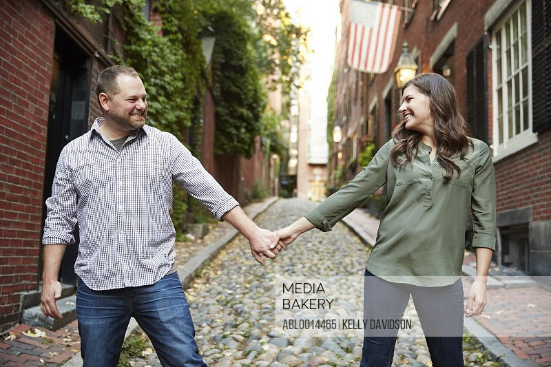 Couple Holding Hands on Street Smiling