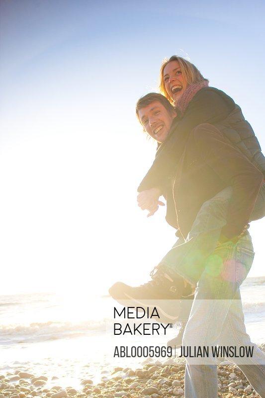 Woman riding piggyback on man on the beach