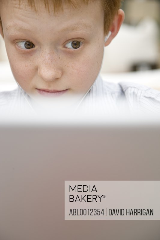 Close up of a boy wearing earphones and using a laptop computer