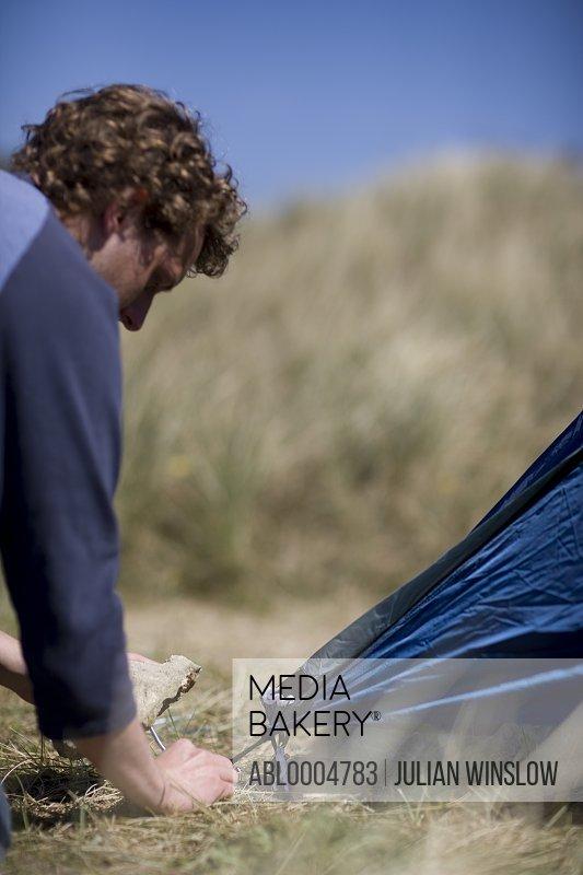 Close up of young man fixing tent peg