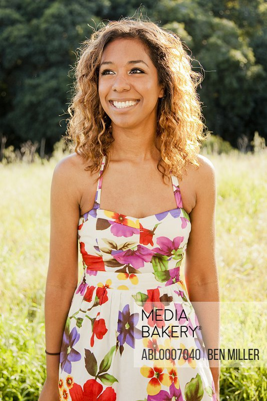 Smiling Young Woman in Floral Dress Outdoors