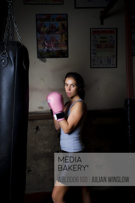 Woman boxer standing by punching bag