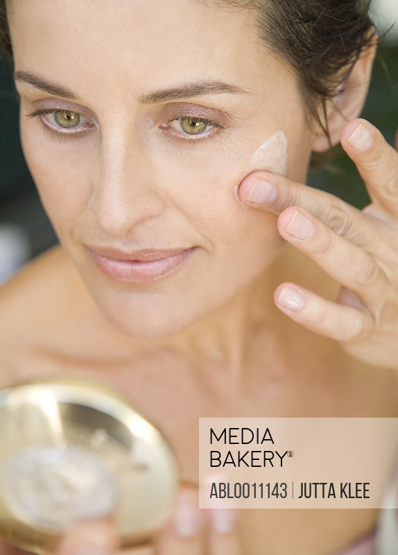 Close up of woman applying moisturizing cream and looking into mirror