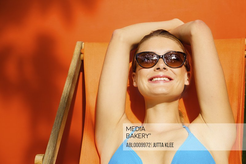 Woman Sunbathing on Orange Deck Chair Smiling