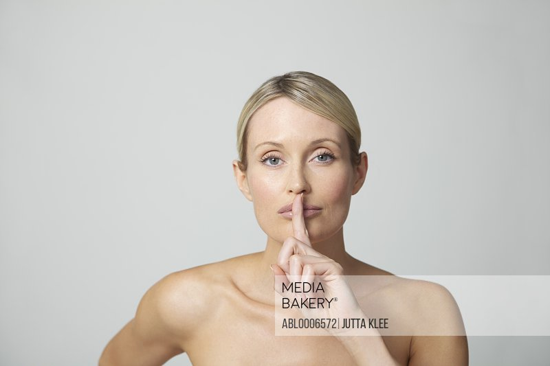 Woman Holding Finger in front of Lips
