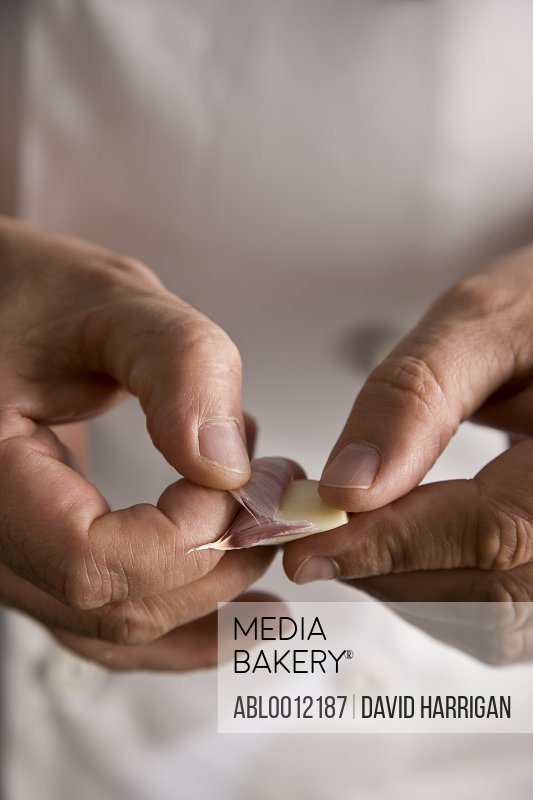 Close up of a chef hands peeling a garlic clove