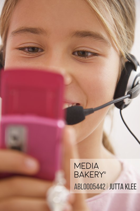 Close up of a smiling girl wearing a headset and holding a mobile phone