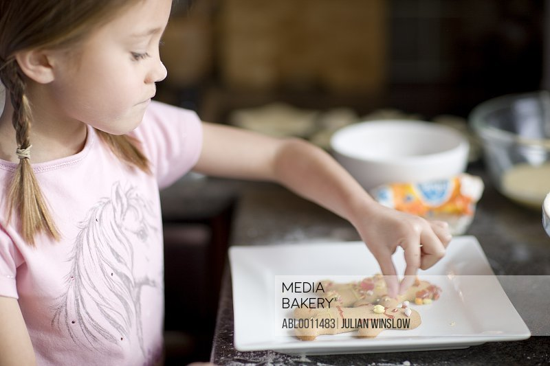 Young girl decorating ginger bread man<br><br><span style='color: red'>Cannot be used in finacial, banking or investment industry in the United Kingdom thru November 21, 2021.</span><br><br>