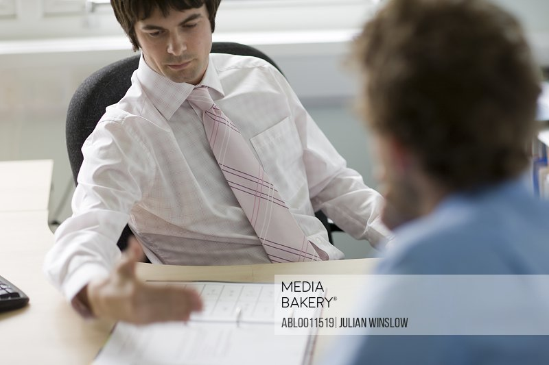 Portrait of young businessman talking to colleague