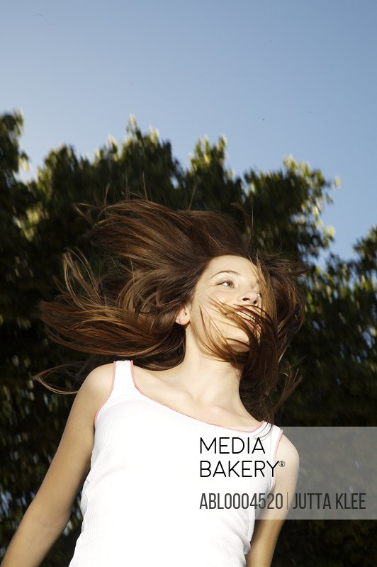 Portrait of a young woman jumping mid air