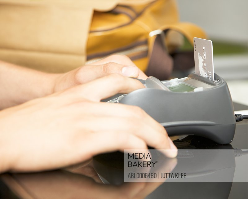 Man's Hands Typing Pin into Credit Card Reader