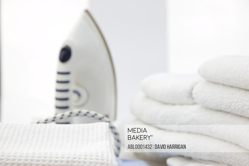 Close up of an iron and a stack of white towels