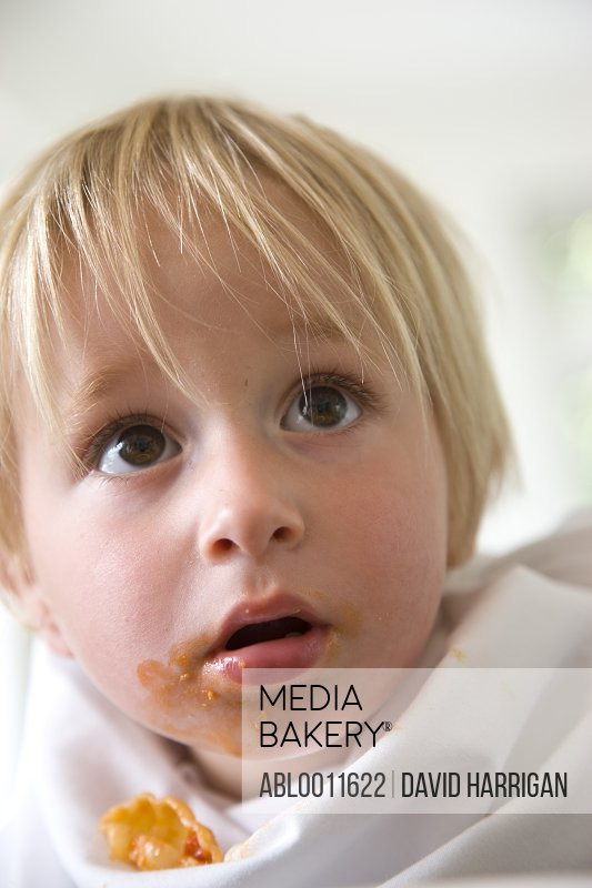 Close up of young blonde boy with pasta sauce over mouth