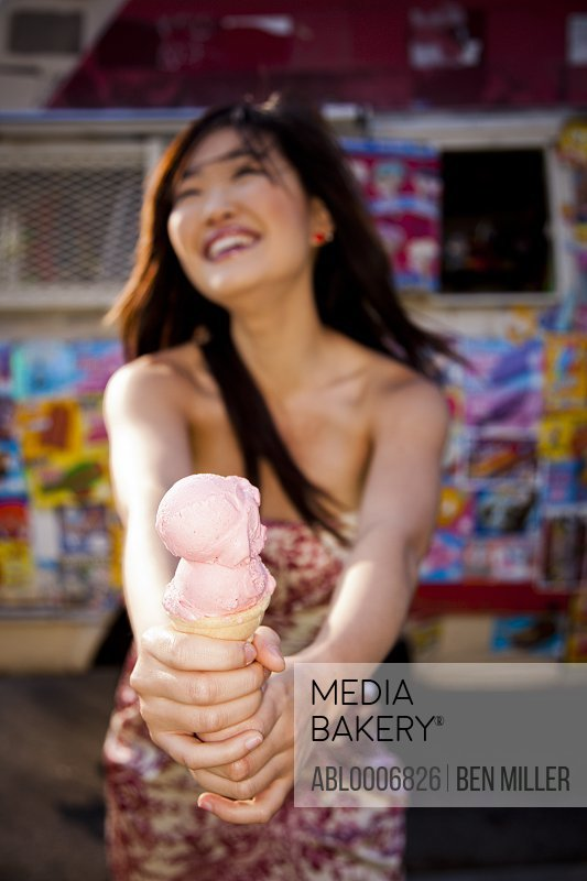 Smiling Young Woman Holding Strawberry Ice Cream Cone