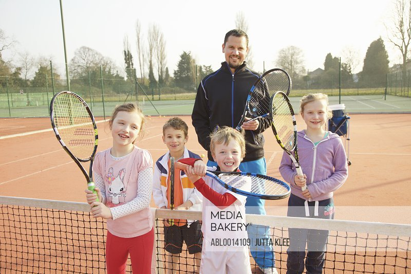 Portrait of Children and Coach on Tennis Court