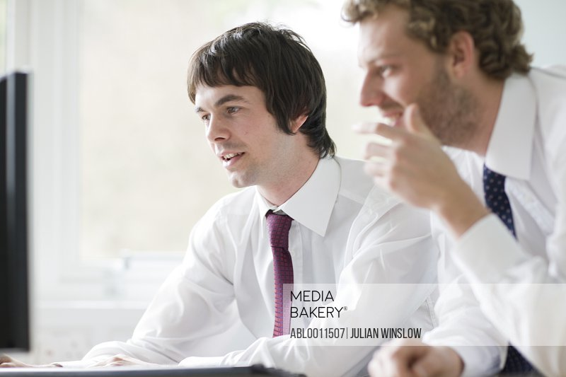 Two young businessmen leaning on desk