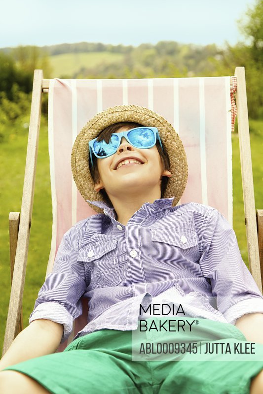 Smiling Boy Wearing Straw Hat and Sunglasses Sitting on Deck Chair