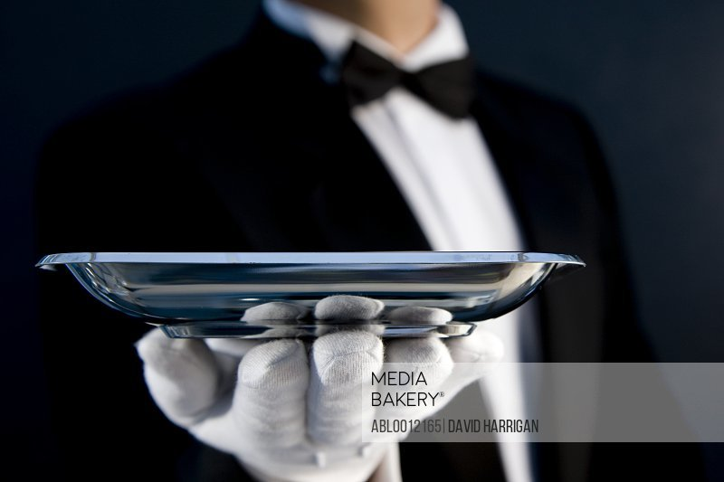 Close up of a waiter wearing white gloves holding a  silver tray in his hand