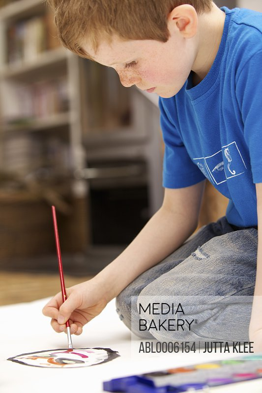 Young boy kneeling on floor painting with watercolors