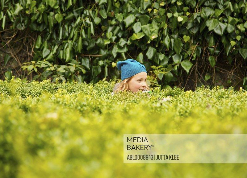 Young Girl Standing Behind Garden Hedge
