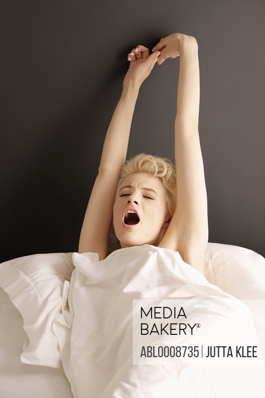 Young Woman in Bed Stretching and Yawning
