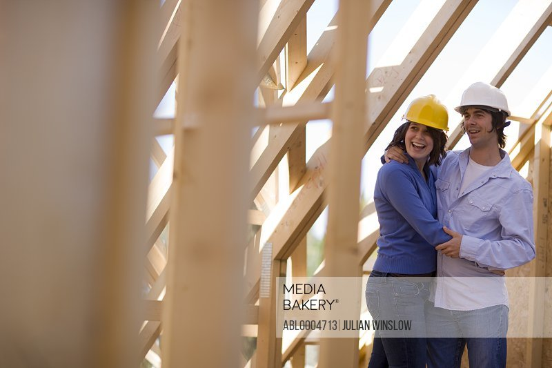 Couple at construction site embracing and laughing