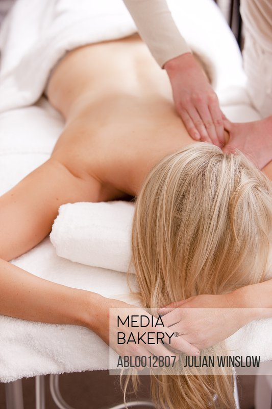 Woman lying on stomach on a massage table receiving a massage
