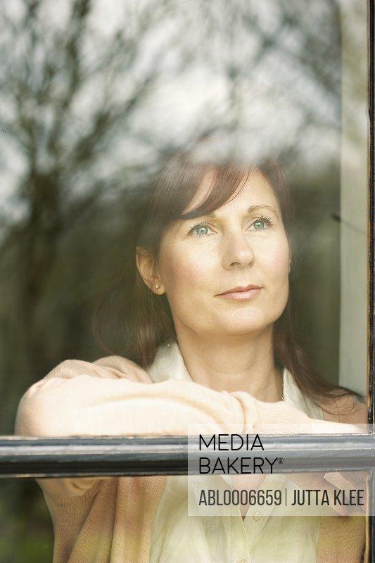 Woman Standing behind Window