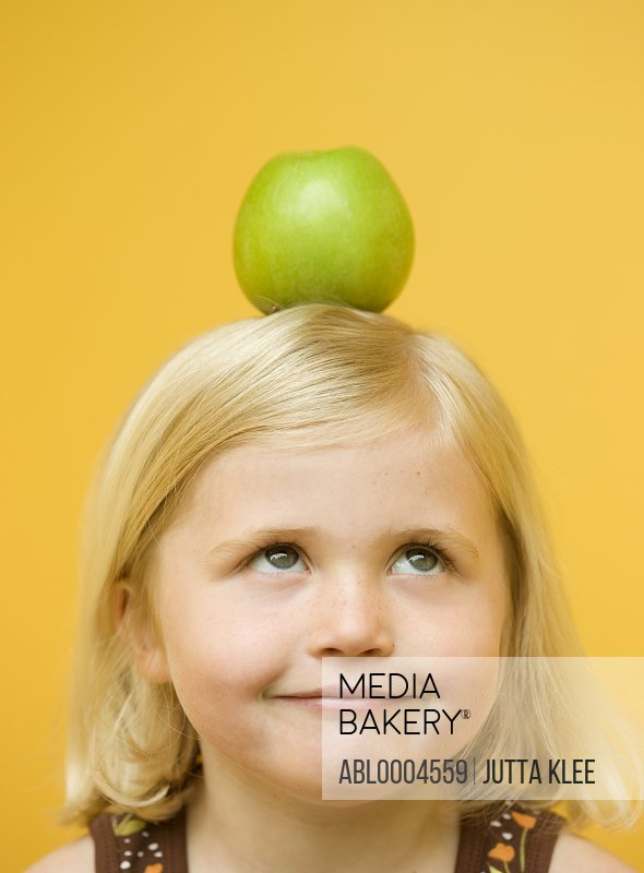 Girl with a green apple on top of her head looking up
