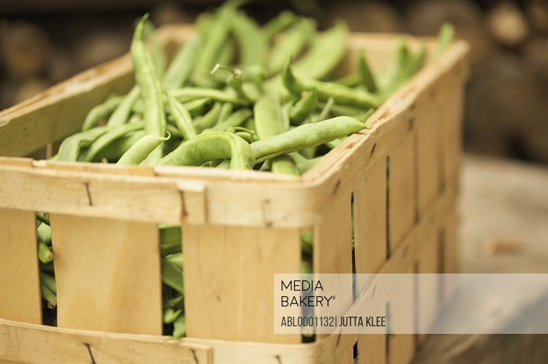 Close up of a wooden crate filled with broad beans
