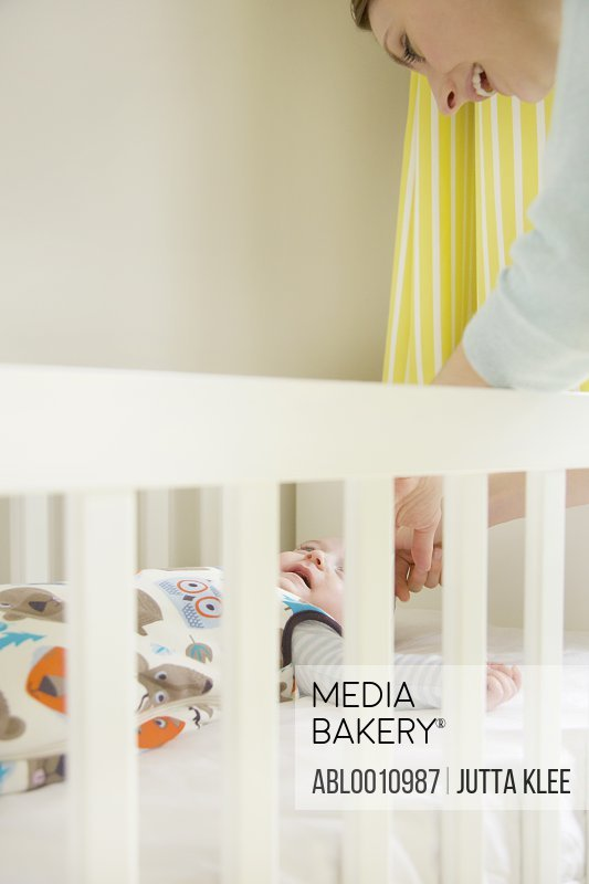 Mother Leaning over Crib Caressing Baby