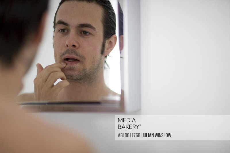 Young man checking his lips in the bathroom cabinet mirror