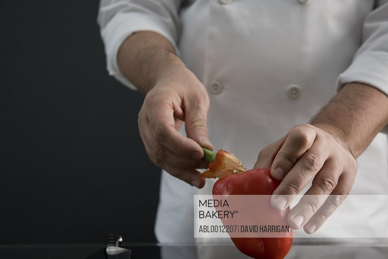 Close up of a chef hand holding and coring a red pepper