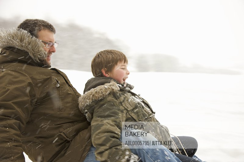 Father and son sledding in the snow